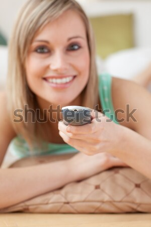 Close-up of a blond woman watching TV lying on the floor  Stock photo © wavebreak_media