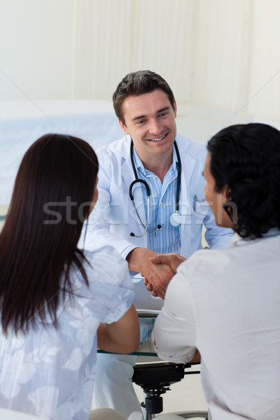 Smiling doctor explaining diagnosis to a couple during a visit Stock photo © wavebreak_media