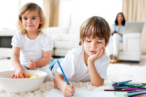 Serious little boy drawing and his sister eating chips lying on the floor Stock photo © wavebreak_media