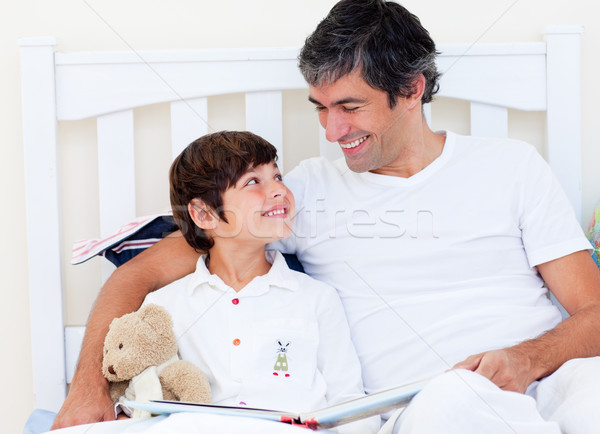 Attentive father reading with his son sitting on a bed Stock photo © wavebreak_media