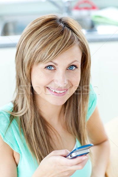 Happy young woman sending a text smiling at the camera in the kitchen Stock photo © wavebreak_media