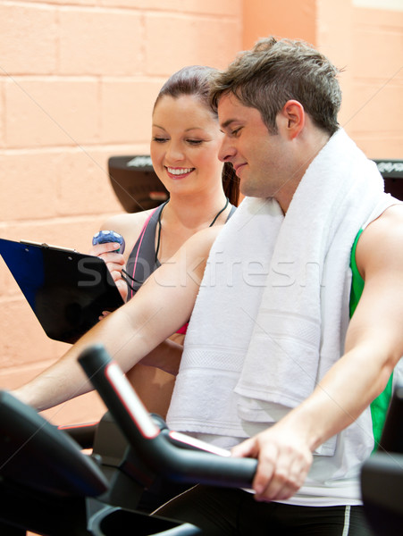 Stock photo: Handsome male athlete exercising on a bicycle with his personal coach in a fitness center