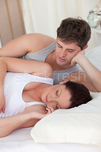 affectionate young man looking at his pregnant wife sleeping both lying on the bed at home Stock photo © wavebreak_media