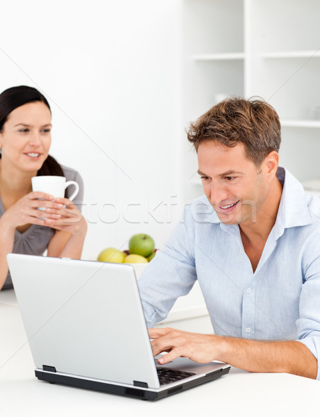 Lovely woman drinking coffee while her husband is working Stock photo © wavebreak_media