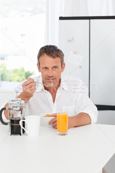 Handsome man having his breakfast in the kitchen at home Stock photo © wavebreak_media