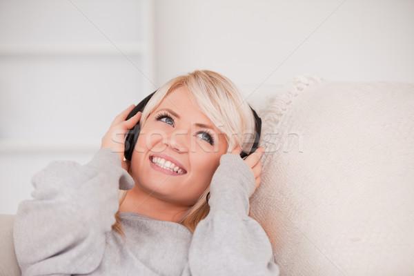 Bájos fiatal szőke nő fejhallgató kanapé Stock fotó © wavebreak_media