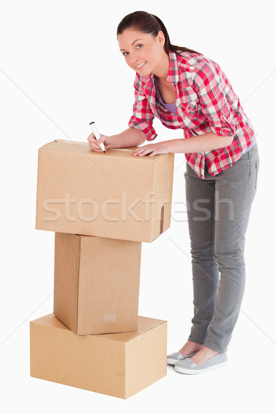 Good looking woman writing on cardboard boxes with a marker while standing against a white backgroun Stock photo © wavebreak_media