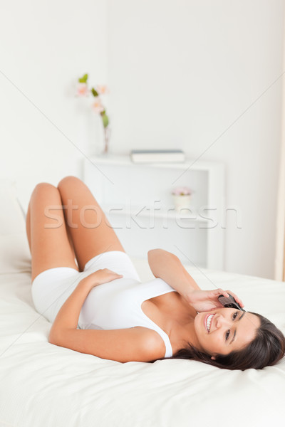 dark-haired woman lying on bed in bedroom on the phone Stock photo © wavebreak_media