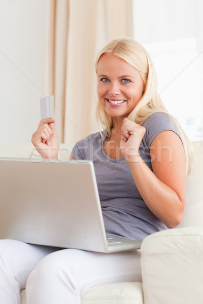 Stock photo: Portrait of a beautiful blond woman shopping online in her living room