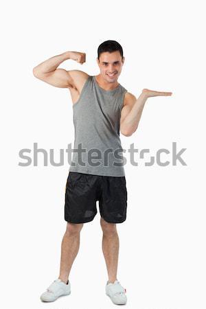 Fiatalember mutat bicepsz bemutat fehér sport Stock fotó © wavebreak_media