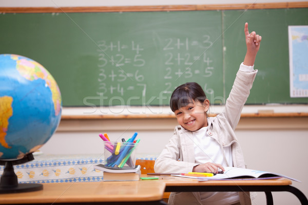 Schoolgirl raising her hand to answer a question in a classroom Stock photo © wavebreak_media