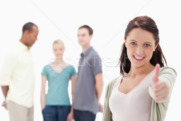 Close-up of a woman smiling and giving the thumbs-up with friends chatting in background Stock photo © wavebreak_media