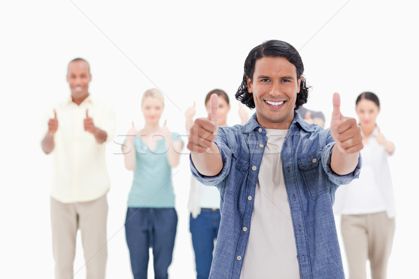 Stock photo: Close-up of a man smiling with his thumbs-up with people behind against white background