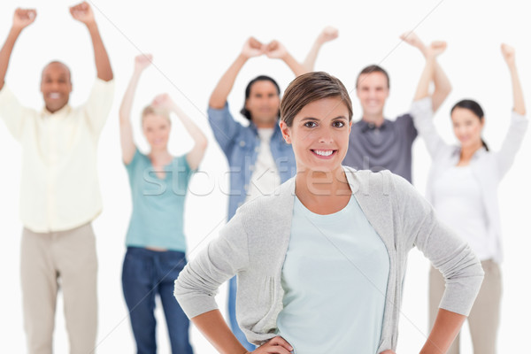 Woman with her hands on hips with people behind raising their arms against white background Stock photo © wavebreak_media