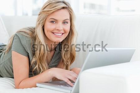 Nő laptopot használ hazugságok kanapé mosolyog néz Stock fotó © wavebreak_media