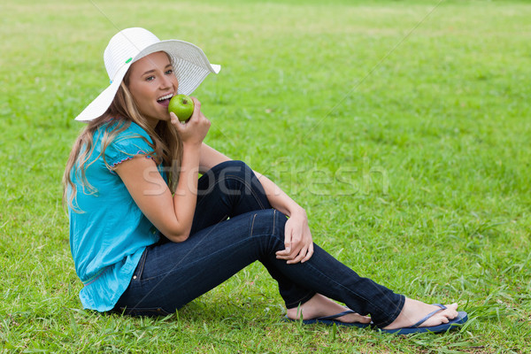 Young girl wearing a hat while sitting down on the grass and eating a green apple Stock photo © wavebreak_media