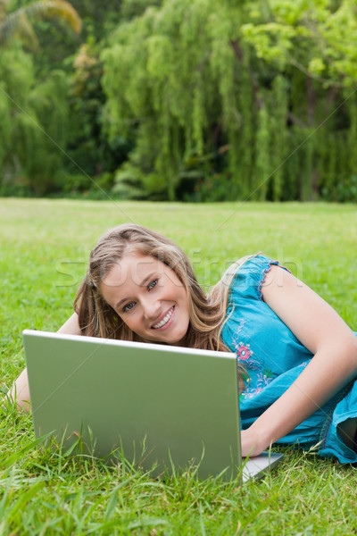 Genç gülen kız dizüstü bilgisayar kullanıyorsanız çim bakıyor Stok fotoğraf © wavebreak_media