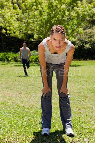 woman bending over to recover while a man is running towards her in the background Stock photo © wavebreak_media