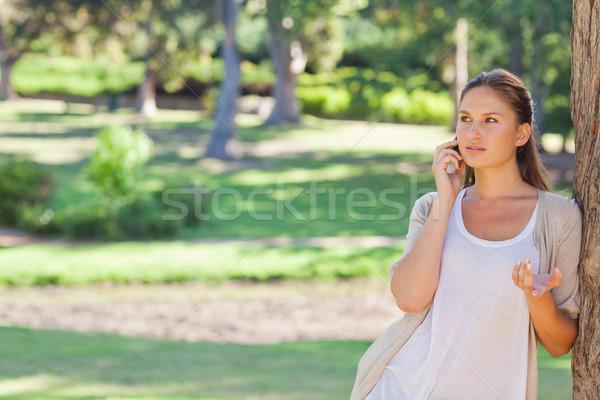 Nő beszél mobiltelefon dől fa fiatal nő Stock fotó © wavebreak_media