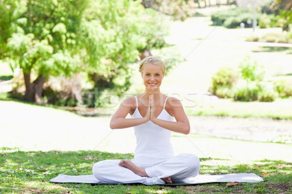 Uśmiechnięty młoda kobieta posiedzenia jogi pozycja trawnik Zdjęcia stock © wavebreak_media