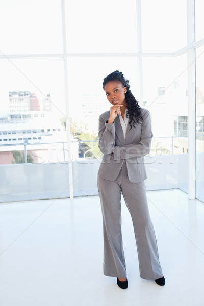 Young serious businesswoman standing upright with her hand on her chin and her arms crossed Stock photo © wavebreak_media