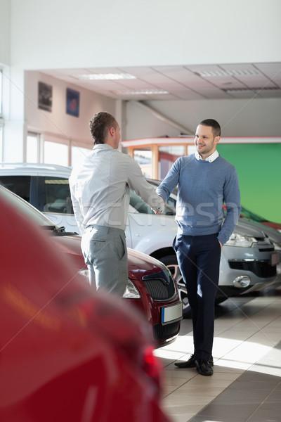 Salesman shaking hand to a customer in a car shop Stock photo © wavebreak_media