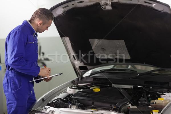 Mecánico portapapeles mirando coche motor Foto stock © wavebreak_media