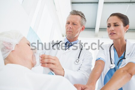 Patient lying in bed in hospital room talking to doctor Stock photo © wavebreak_media