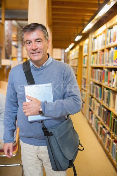 Férfi áll polcok könyvtár tart könyv Stock fotó © wavebreak_media