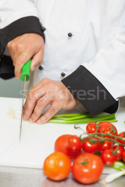 Chef slicing spring onions in the kitchen Stock photo © wavebreak_media