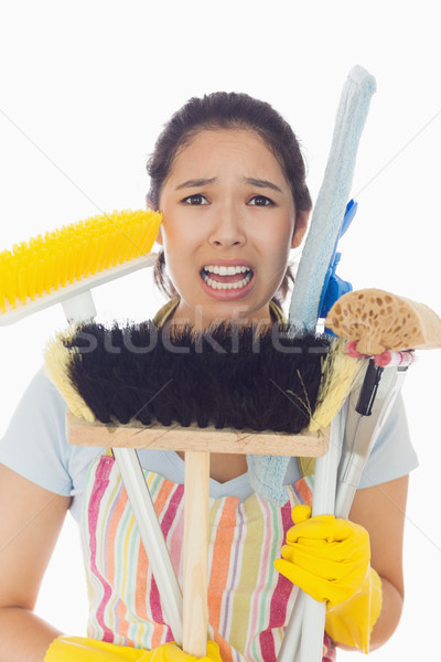 Distressed young woman in apron and rubber gloves holding cleaning tools Stock photo © wavebreak_media
