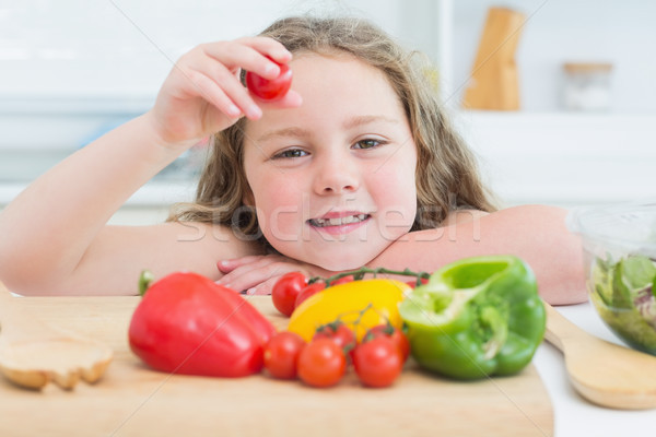 Little girl holding up cherry tomato from the chopping board of vegetables Stock photo © wavebreak_media