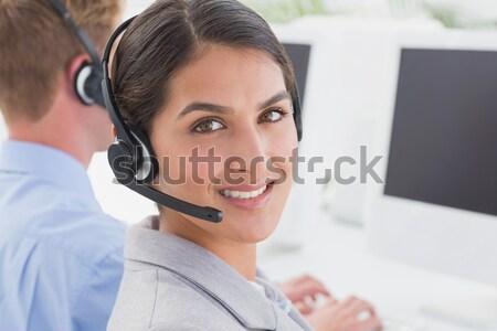Portrait of business woman wearing headset and using laptop Stock photo © wavebreak_media