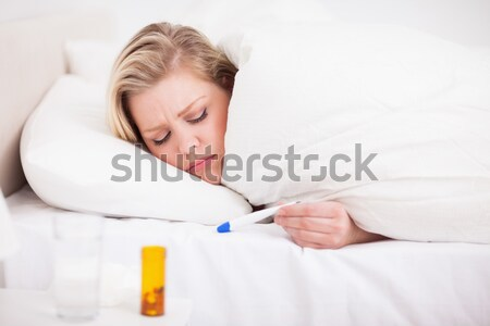 Asleep woman and spilt bottle of pills in bedroom Stock photo © wavebreak_media