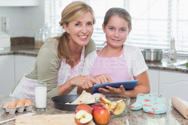 Stock photo: Happy mother and daughter preparing cake together