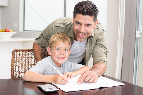 Cheerful father helping son with math homework at table Stock photo © wavebreak_media