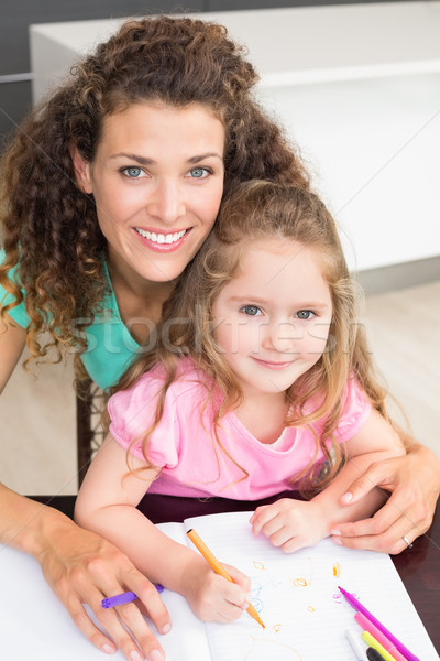 Smiling mother and daughter colouring together at the table Stock photo © wavebreak_media