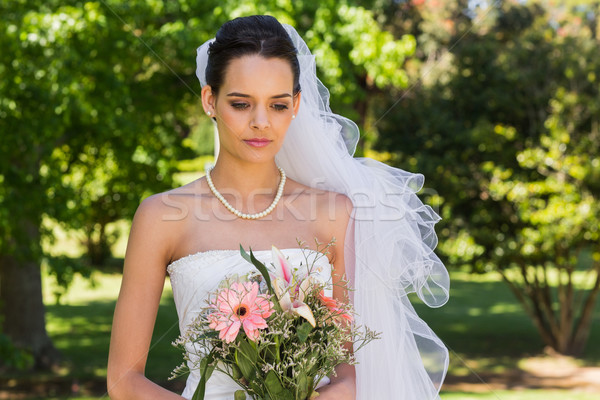 Serious beautiful bride with bouquet in park Stock photo © wavebreak_media