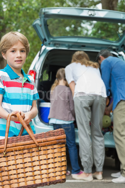 Boy with picnic basket while family in background at car trunk Stock photo © wavebreak_media