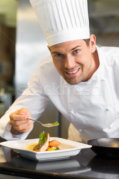 Smiling male chef garnishing food in kitchen Stock photo © wavebreak_media