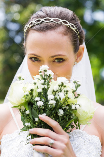 Stock photo: Young bride peeking over bouquet in garden
