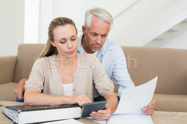 Serious couple calculating their bills at the couch Stock photo © wavebreak_media