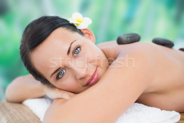 Stock photo: Beautiful brunette enjoying a hot stone massage smiling at camer