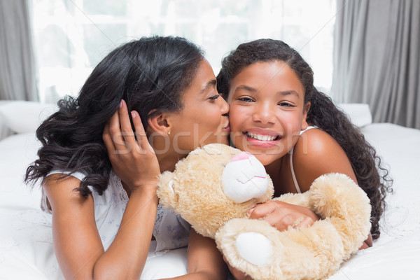 Pretty woman lying on bed with her daughter smiling at camera Stock photo © wavebreak_media