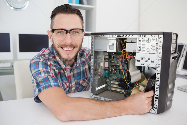 Computer engineer working on broken console smiling at camera Stock photo © wavebreak_media