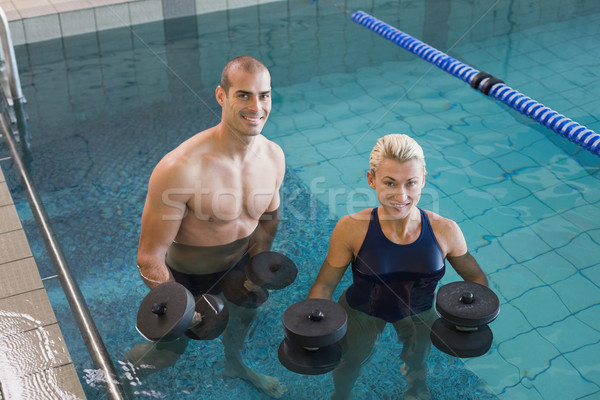 Swimmers working out with foam dumbbells in swimming pool at lei Stock photo © wavebreak_media