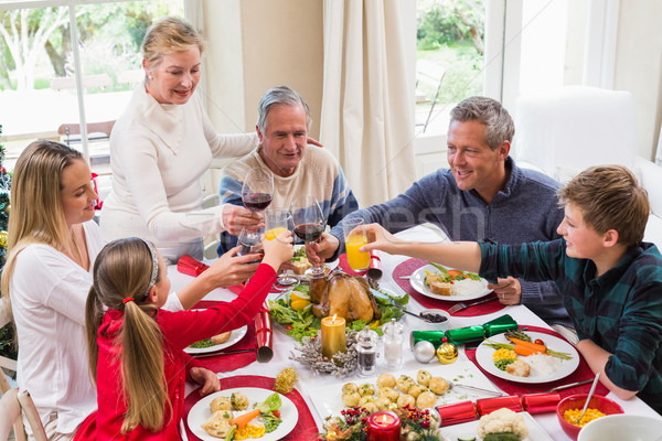 Stock photo: Family toasting with red wine in a christmas dinner