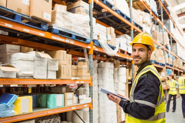 Smiling warehouse manager holding clipboard Stock photo © wavebreak_media