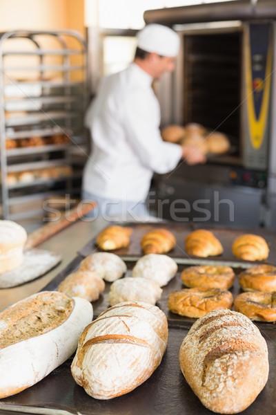 Happy baker taking out fresh loaves Stock photo © wavebreak_media