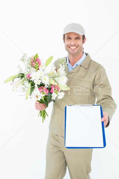 Delivery man with bouquet giving clipboard for signature Stock photo © wavebreak_media